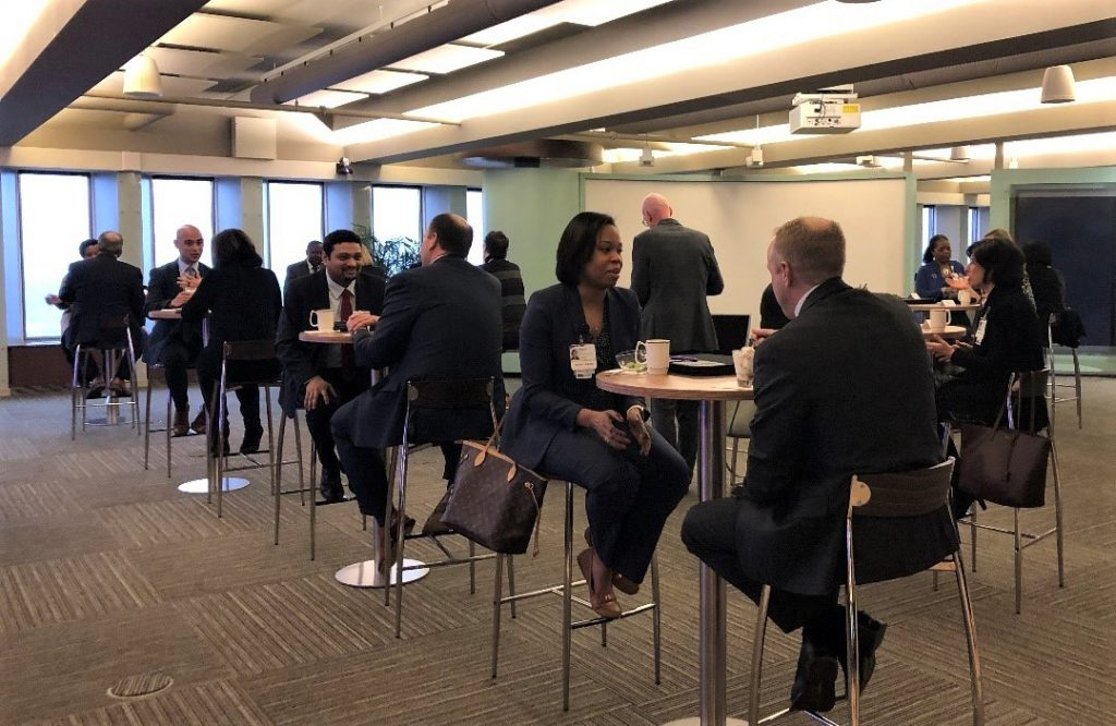 Members of Diversity Leadership Network sit at tables and converse in conference room