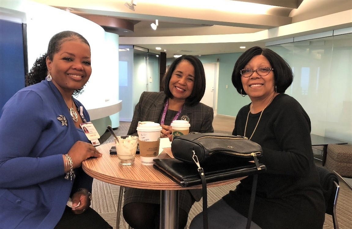 Three women, members of the Diversity Leadership Network at UPMC, sit at a round table together and smile at camera