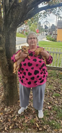 Mary Lou smiles with her two small dogs