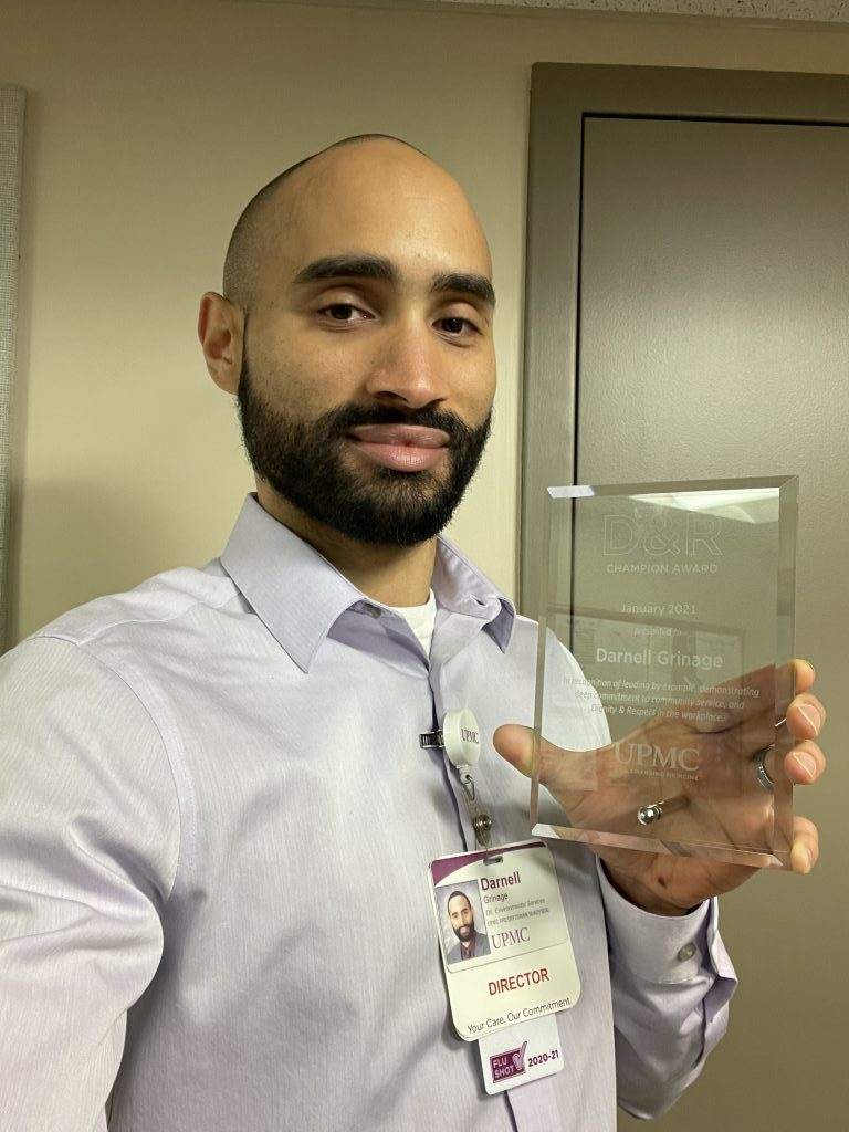 Darnell smiles, holding his award.