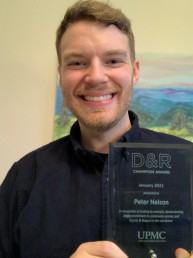 Peter holds his award, smiling.