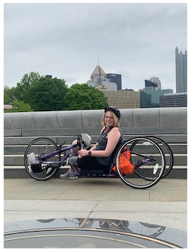 Woman on hand cycle in front of Pittsburgh city skyline.
