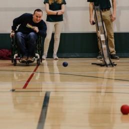 Man in wheelchair enjoying game of bocce, throwing blue ball.
