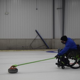 Man in wheelchair on the ice rink, practicing curling.