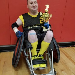 Man in wheelchair holding a gold trophy after playing basketball.