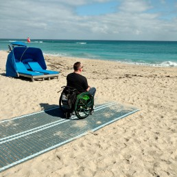 Man in wheelchair on the beach, sitting on a sand mat.